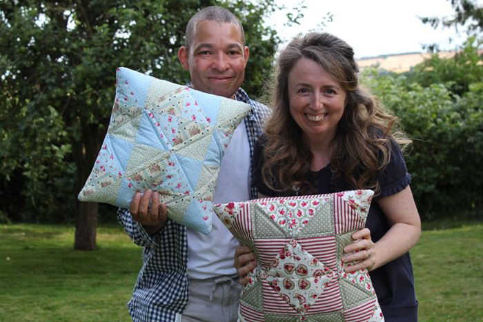 Paul and Cindy holding completed patchwork cushions