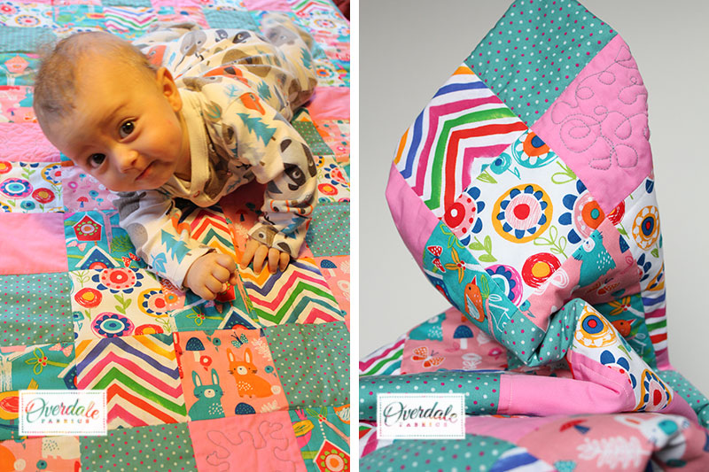baby with pink and blue quilt