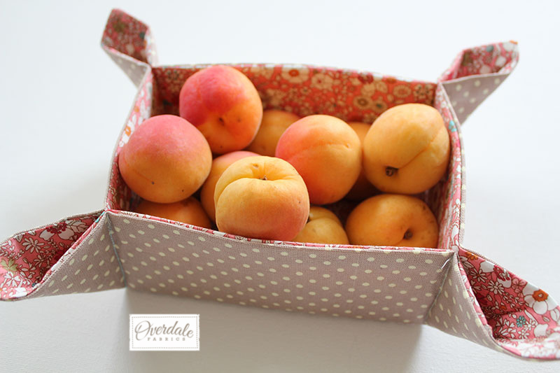 Decorative fabric basket filled with apricots.