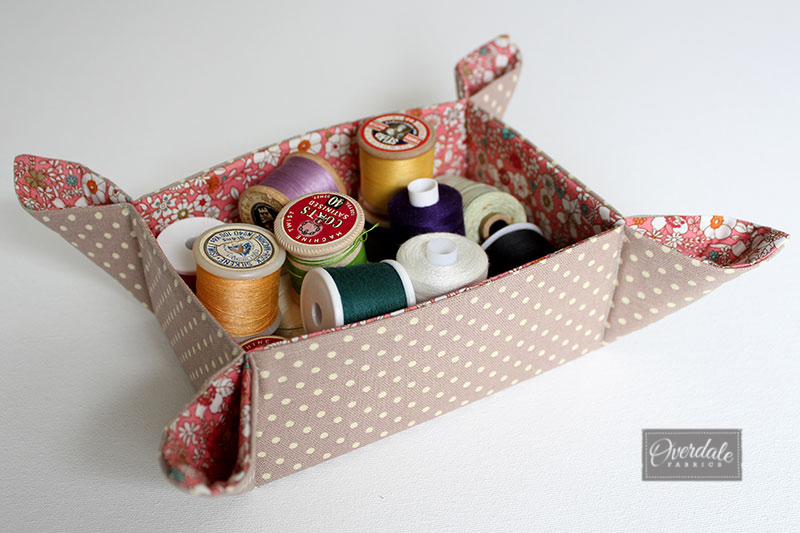 Fabric basket filled with cotton reels.