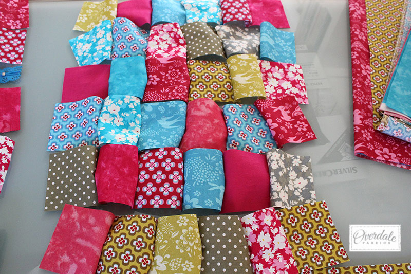 Arranging fabric squares for a quilted panel.