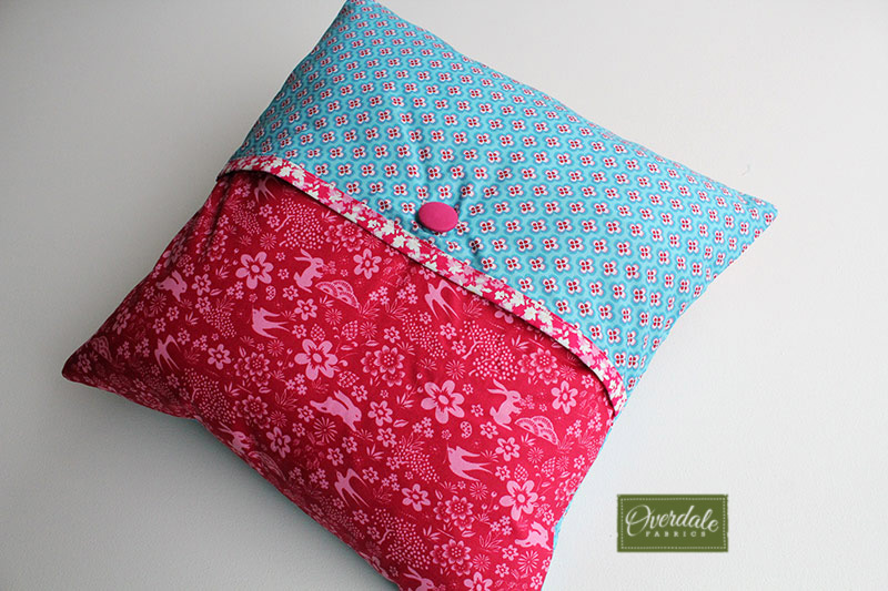 Back of a cushion cover with an envelope opening and button detailing.